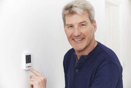man programming thermostat